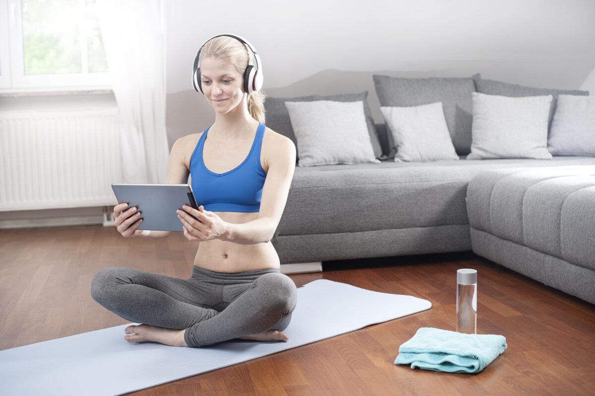 Junge Frau macht Sport Online Kurs im Wohnzimmer