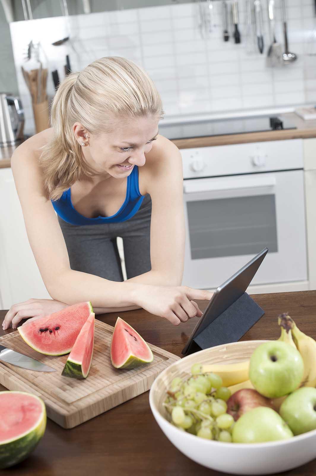 Junge Frau sucht Rezept online auf I Pad in Kueche