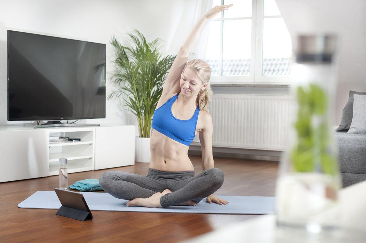 Junge Frau macht Yoga zu hause im Wohnzimmer
