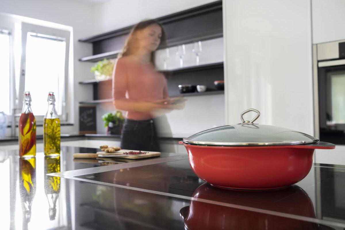 Junge Frau arbeitet in der Küche und ein roter Kochtopf steht im Vordergrund