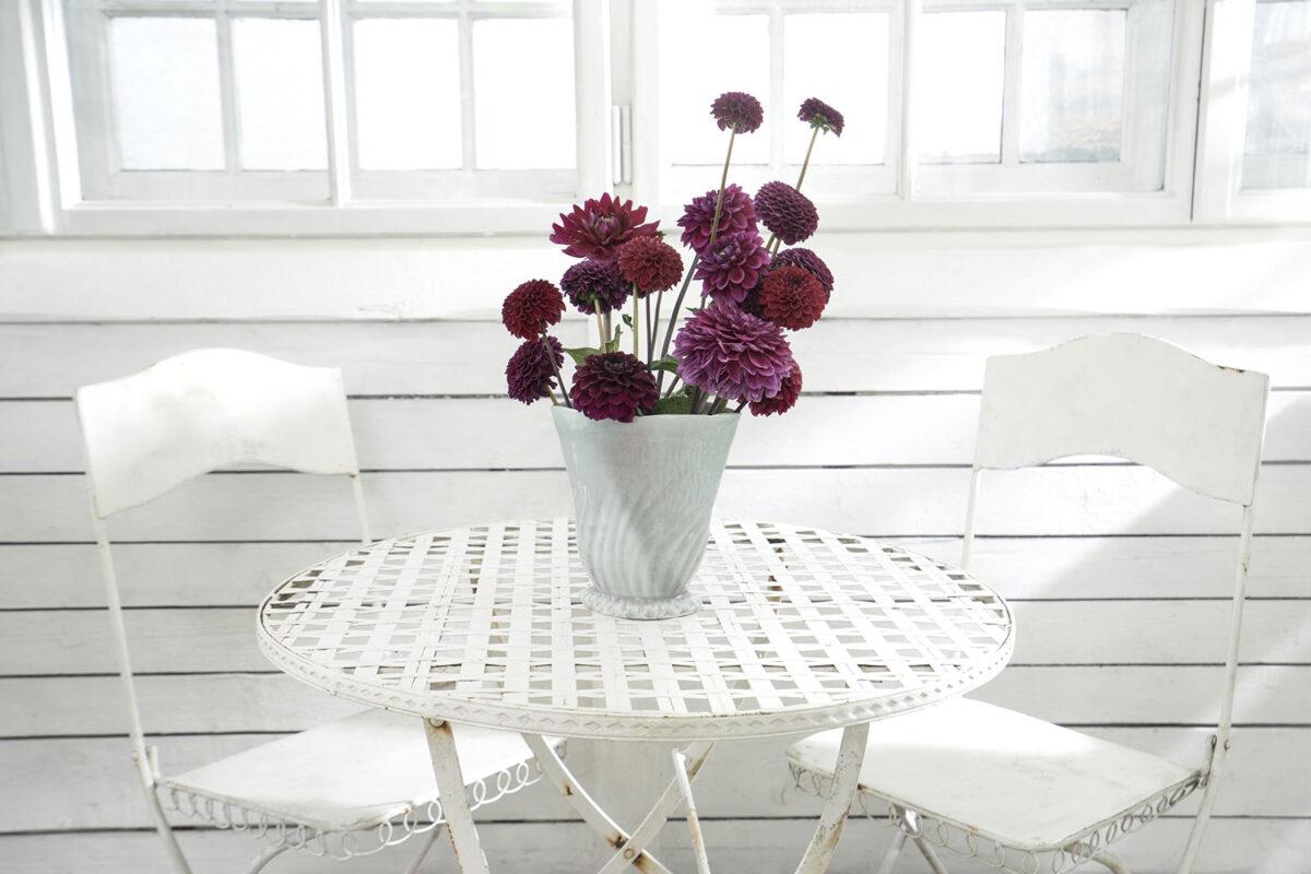 Weisser Metalltisch mit zwei Stuehlen und Blumen in einer Vase