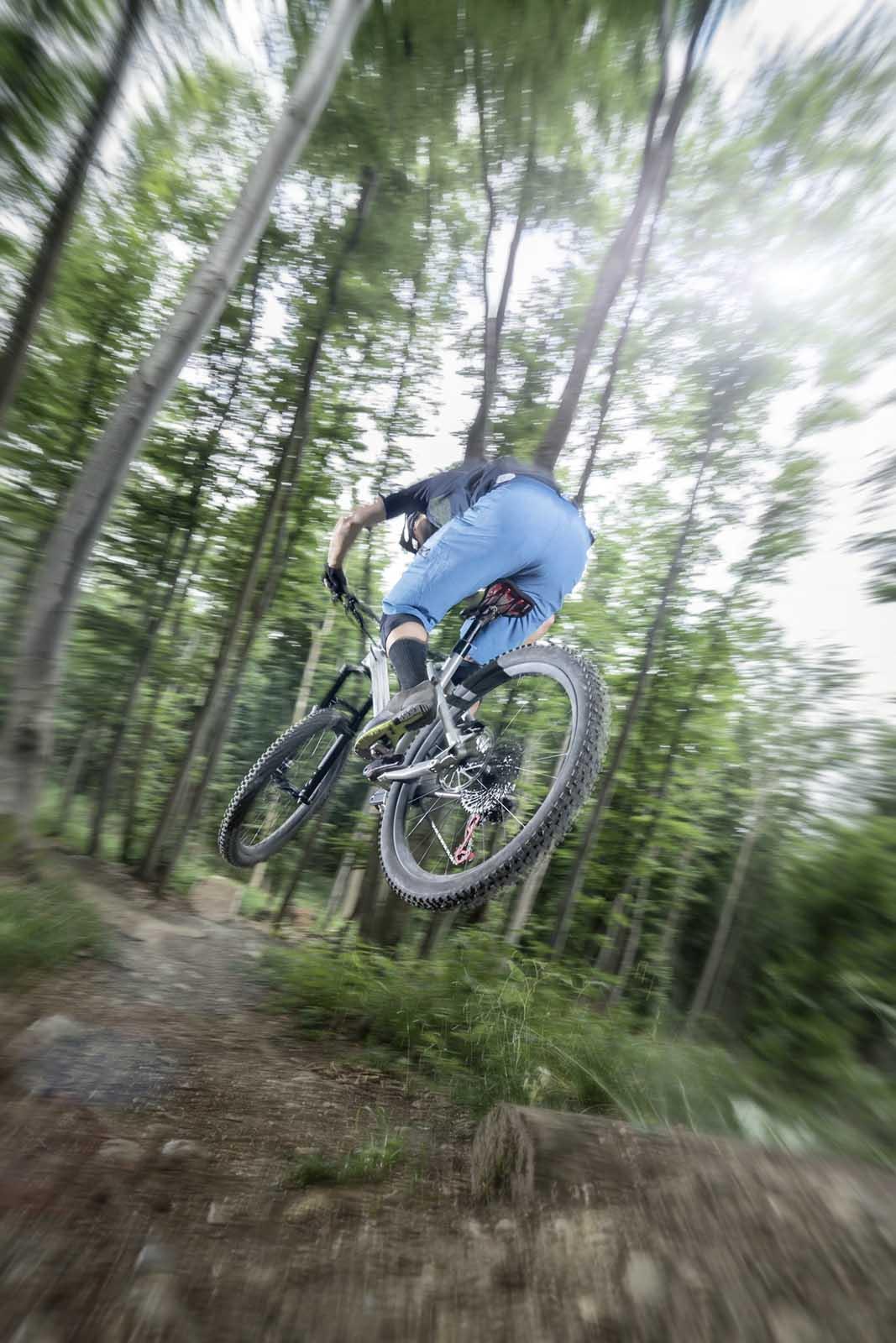 Sportfotografie-München-Mountainbike-MTB-Mann-springen-im-Wald-von-hinten