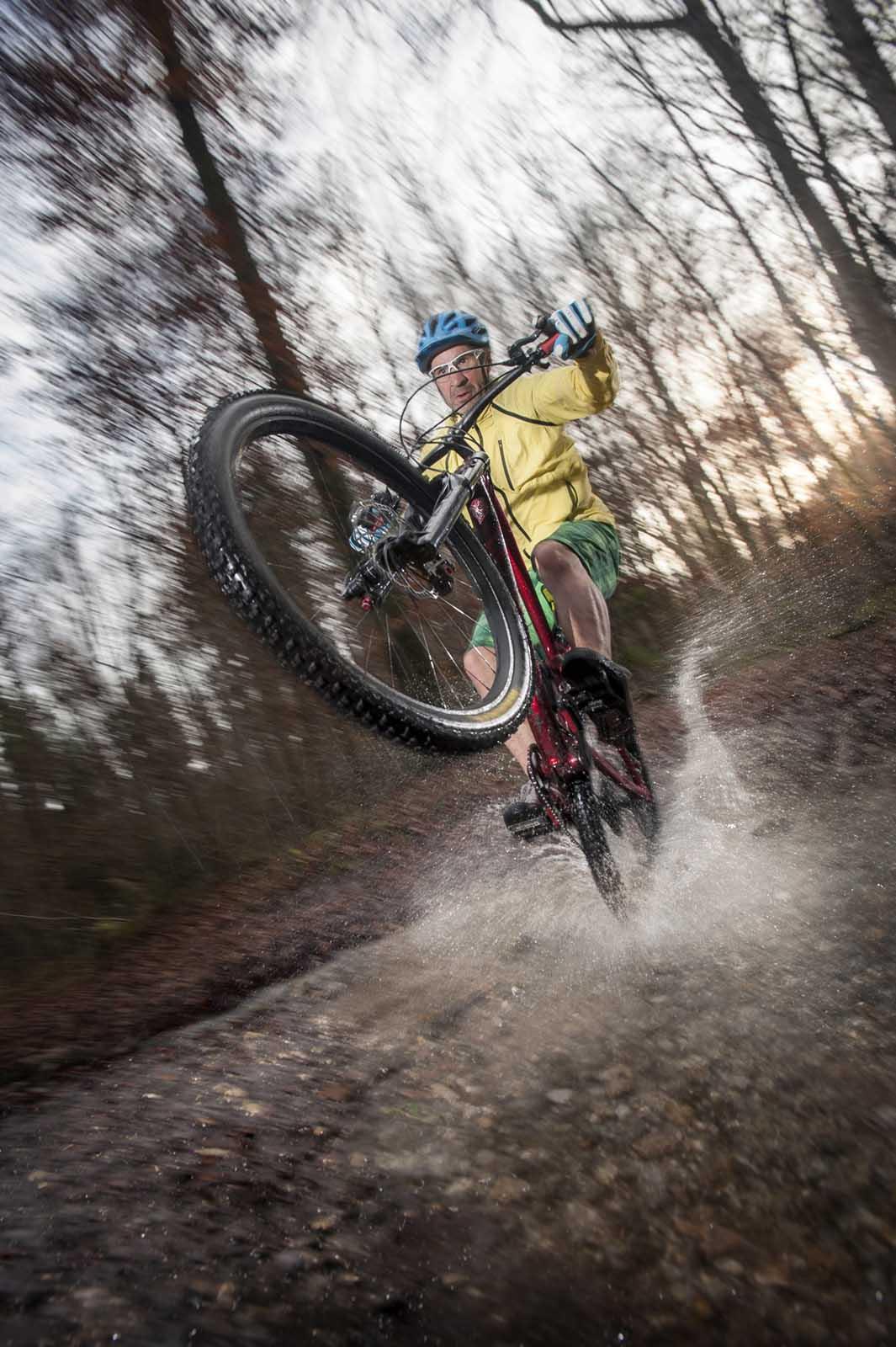 Sportfotografie-München-Mountainbike-MTB-Mann-durch-Wasser-auf-Hinterrad-Wasser-spritzen