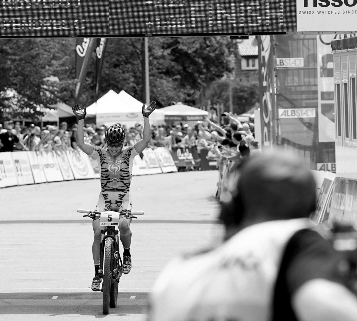 Sportfotografie-München-Mountainbike-MT-Frau-Jubel-Zieleinfahrt-Cross-Country-Rennen-schwarz-weiss