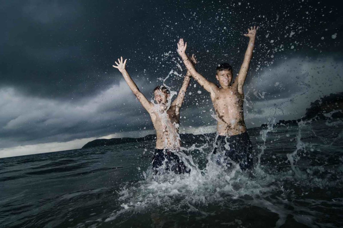 Werbefotografie-Lifestyle-Jungen-Meer-spritzen Wasse-dramatische Wolken