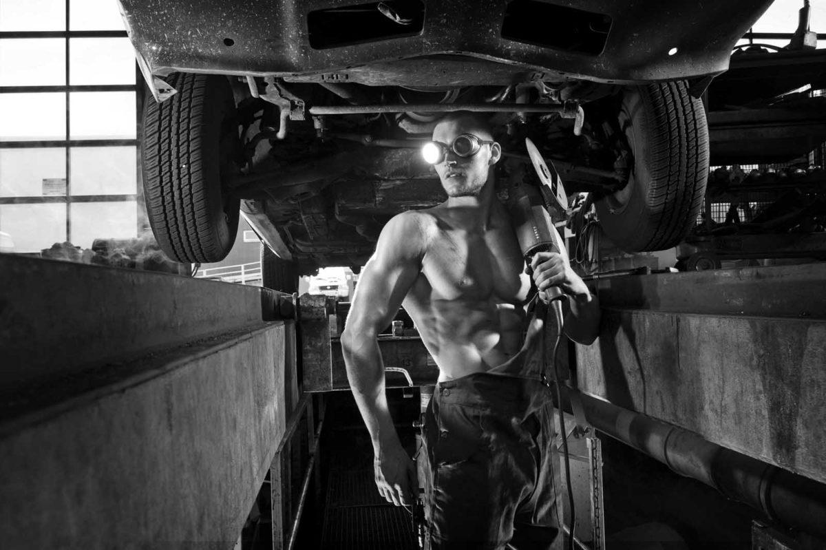 Werbefotografie-Lifestyle-Muskeln-Mann-freier Oberkörper-Werkstatt-Auto-schwarz-weiß