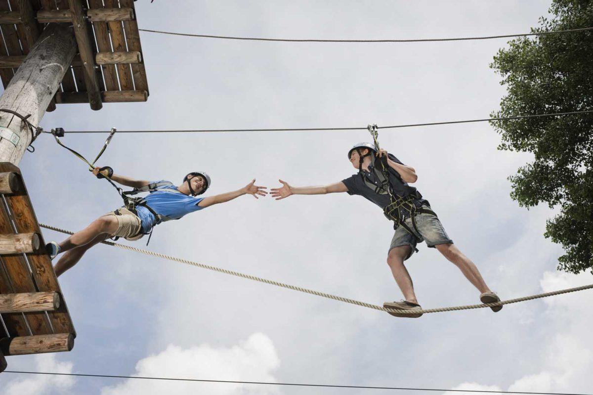 Werbefotografie-Lifestyle-Klettergarten-zwei Teenager-Hände reichen-Vertrauen