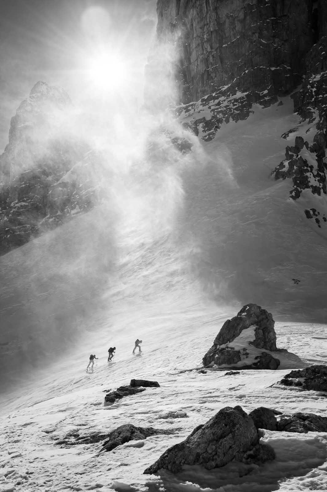 Sportfotografie-Wintersport-Ski-Skitour-Gruppe-Aufstieg-Schneesturm-Sonne-schwarz-weiss-Sella Stock-Südtirol