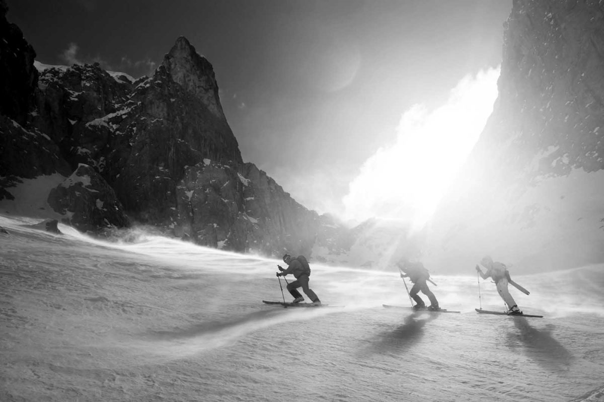Sportfotografie-Wintersport-Ski-Skitour-Gruppe-steiler-Aufstieg-stürmisch-sonnig-von-Val Setus-Südtirol-Sella Stock-schwarz-weiss