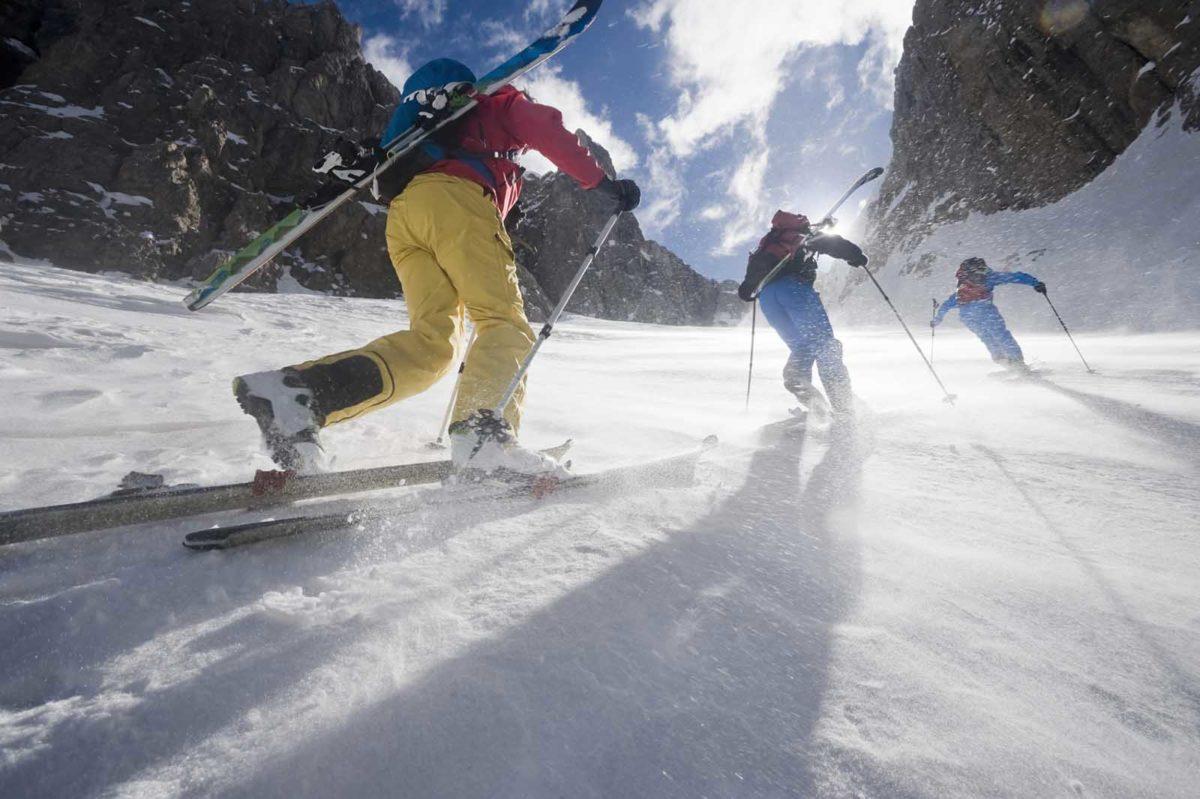 Sportfotografie-Wintersport-Ski-Skitour-Gruppe-steiler-Aufstieg-stürmisch-sonnig-von-hinten-Val Setus-Südtirol-Sella Stock