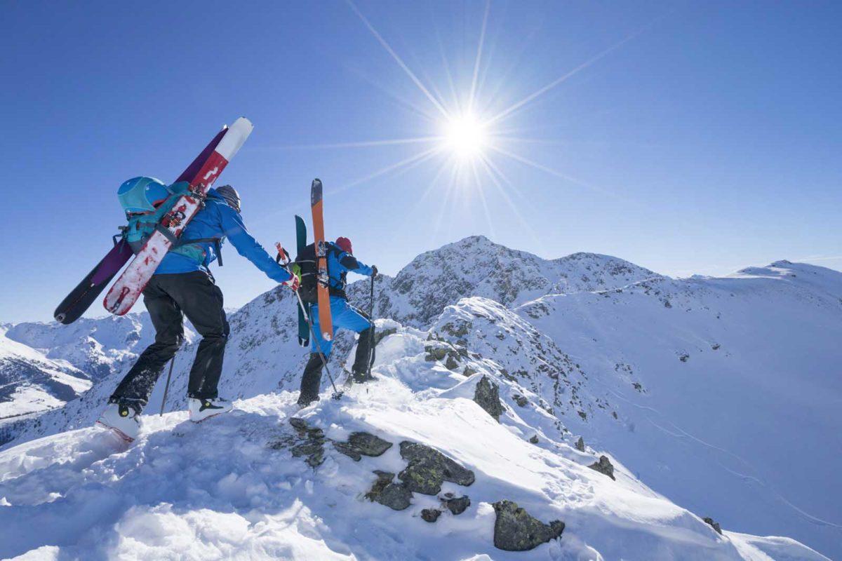 Sportfotografie-Wintersport-Ski-Skitour-zwei-Tourengeher-von hinten-Gratüberquerung-Sonne-Alpbachtal