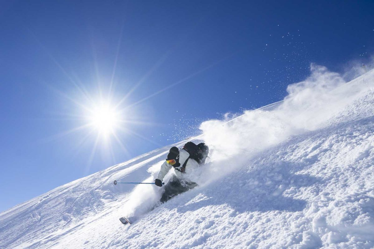 Sportfotografie-Wintersport-Ski-Freeride-rasante-Abfahrt-Sonne-Schnee-staubt-Arlberg-Tirol